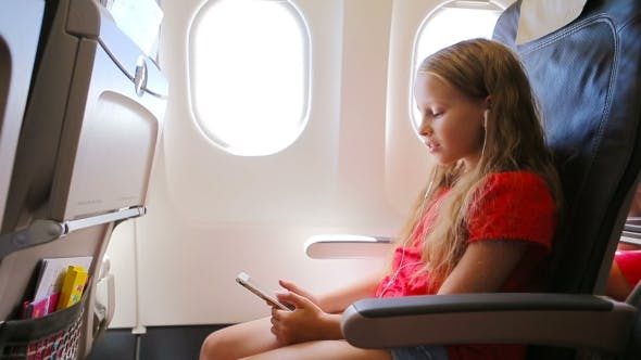 Thumbnail for Adorable Little Girl Traveling By An Airplane. Kid Listening Music Sitting Near Aircraft Window