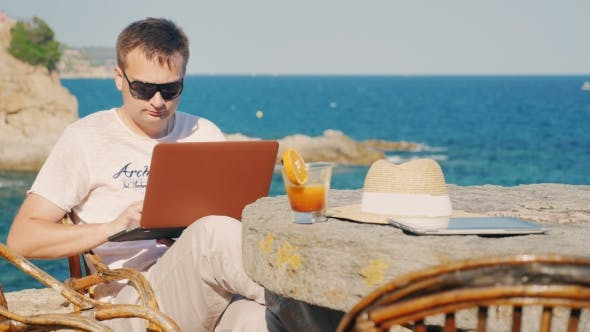 Thumbnail for Man In Sunglasses Work With a Laptop. Against The Background Of The Sea At a Table In a Cafe