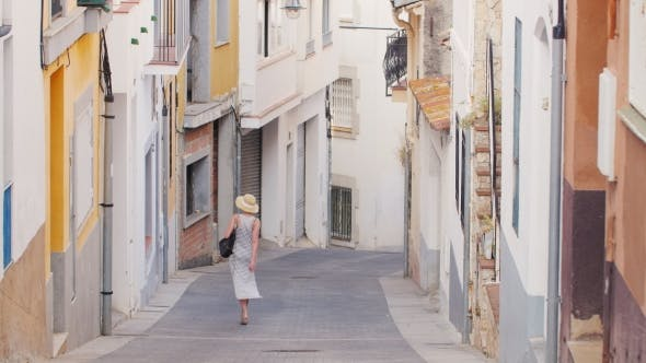 Cover Image for Woman Tourist Goes Down the Narrow Streets of the Old Mediterranean City