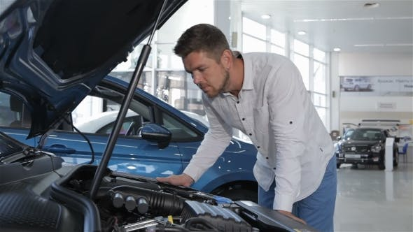 Thumbnail for Man Looks at the Engine Compartment of the Car at the Dealership