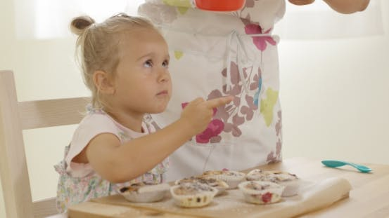 Thumbnail for Child Interested In Sugar Falling On Baked Muffins