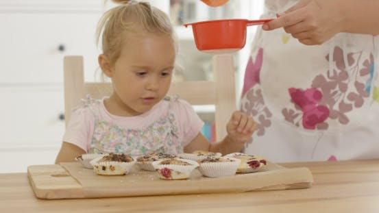Thumbnail for Girl Watching Sugar Fall On Baked Muffins