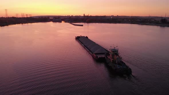 Thumbnail for Aerial View. Sunset Over the Water Channel. The Cargo Barge Goes Towards the Locks. A Bulk Carrier