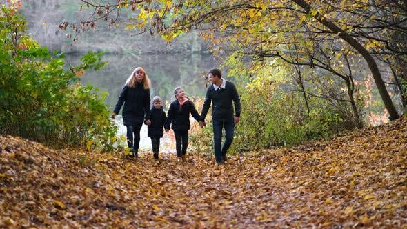 A Happy Family is Walking in the Autumn Park