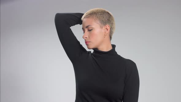 Thumbnail for Blonde with Short Haircut in Studio Poses for Camera on Grey Ideal Skin