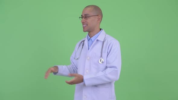 Thumbnail for Happy Bald Multi Ethnic Man Doctor Presenting Something