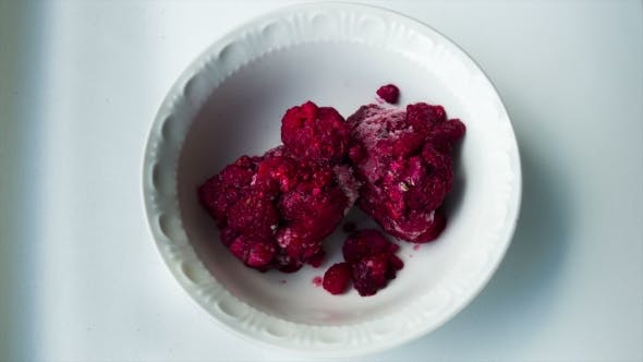Thumbnail for Frozen Raspberries Melting In a Plate On a White Background.