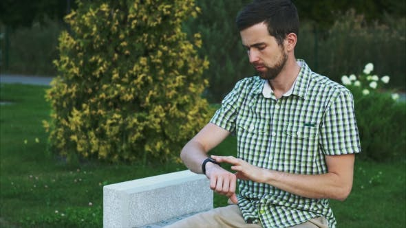 Thumbnail for Young Man Using Smartwatch While Sitting In The Park