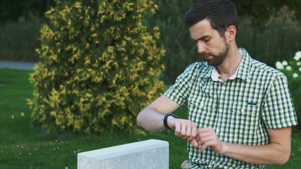 Young Man Using Smartwatch While Sitting On The Bench In The Park