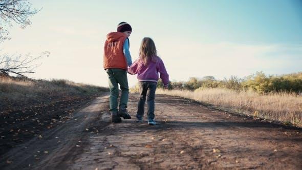 Thumbnail for zwei kleine kinder zu Fuß entlang einer unbefestigten straße
