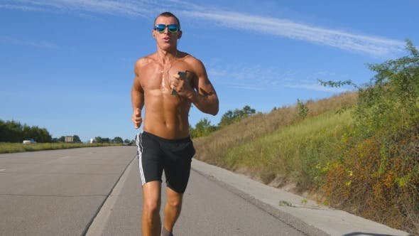 Cover Image for Young Smiling Muscular Man In Sun Glasses Jogging At Highway And Listening Music In Headphones From