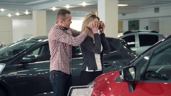 Thumbnail for Man Surprises Wife Or Girlfriend In Car Dealership, Showing New Car