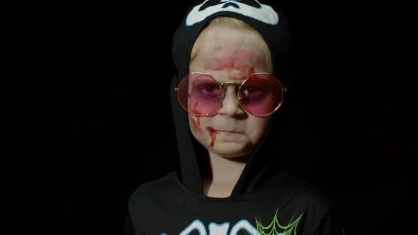 Halloween, Angry Girl mit Blut Make-up auf Gesicht. Kind als gruseliges Skelett gekleidet, posiert, Gesichter