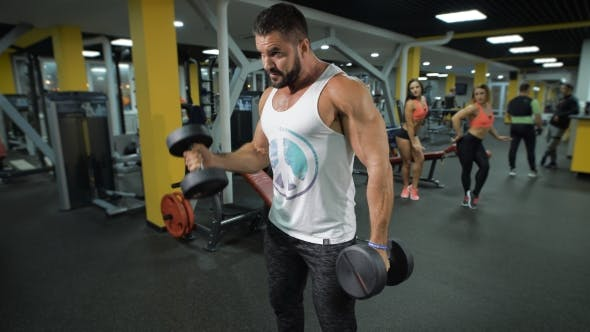 Thumbnail for Muscular Man Exercises With Dumbbells