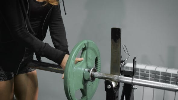 Thumbnail for Girl Sets Weight Plate On Barbell