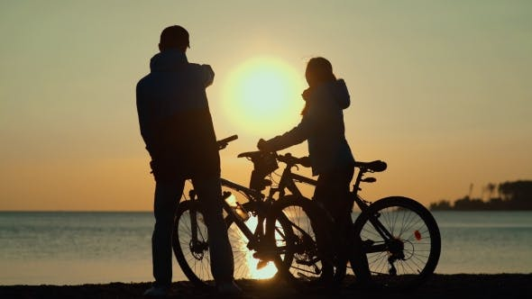 Silhouettes Of Cyclists At Sunset. Male And Female Silhouettes