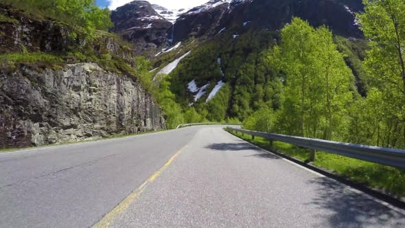 Driving a Car On a Serpentine Road In Norway