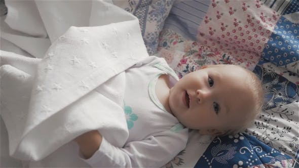 Thumbnail for Little Cute Baby Girl On The Bed Hiding And Playing With Sheets