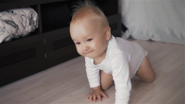 Thumbnail for Cute Baby With Beautiful Blue Eyes On The White Background Creeps. Top View Action Concept