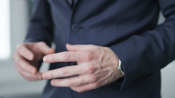 Thumbnail for Businessman buttoning his jacket, making gestures and checking hour on his watch
