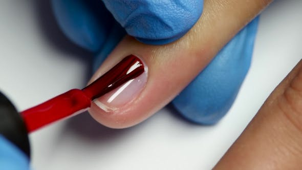 Thumbnail for Master Covers Nails Of Client By a Red Varnish.