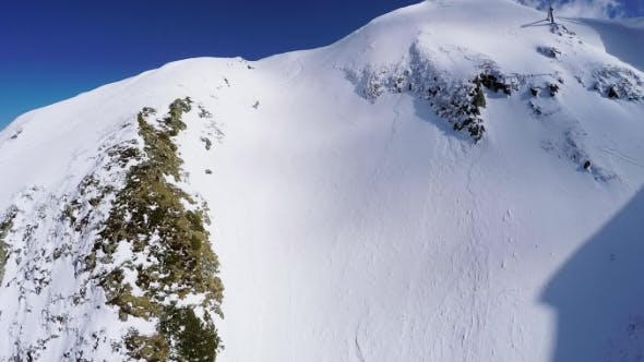 Quadrocopter Shoot Snowboarder Freestyle From Peak Of Snowy Mountain. Extreme
