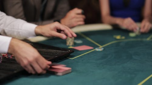 Group of People in Underground Casino Bet. The Dealer Deals The Cards.