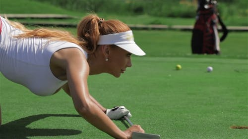 Woman Stands on All Fours in Front of the Hole at the Golf
