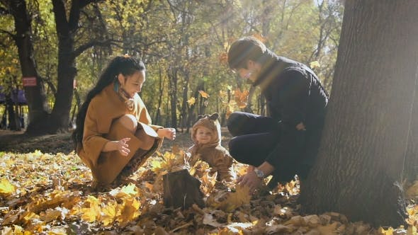 Thumbnail for Happy Family Playing With Autumn Leaves In Park. Mom And Dad Throw Leas Up In The Air. Small Child
