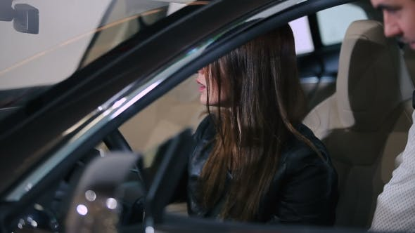 Woman Testing The Electric Car Inside Of Car
