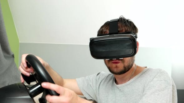 Thumbnail for Man Enthusiastically Playing In Virtual Reality Glasses, Drives a Car Simulator.