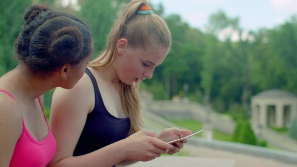 Thumbnail for Blonde Girl Showing Photos On Tablet To African Girlfriend
