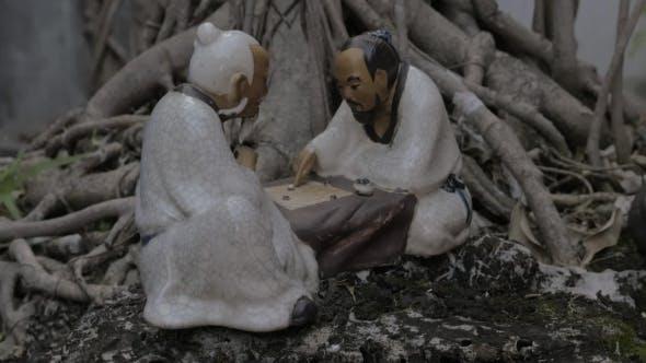 Small Porcelain Figure At Bonsai Tree