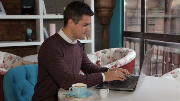 Thumbnail for Man Uses Laptop At The Cafe