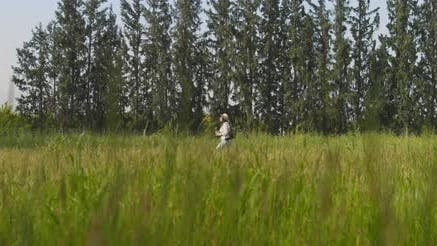 Thumbnail for Woman with hat and backpack walking through the green field,carrying a pot plant