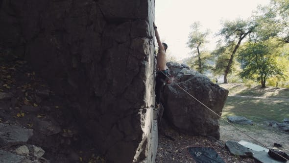 Thumbnail for Man In Cap Descending The Cliff On Rope