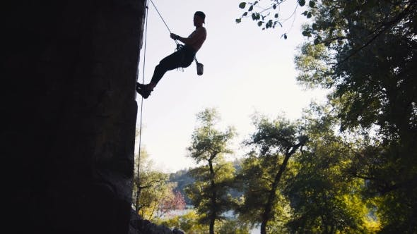 Thumbnail for Silhouette Of Man Climbing On Cliffed Rock Belay