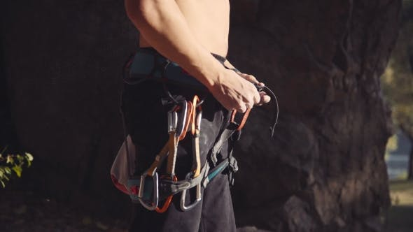 Thumbnail for Topless Climber With Carabiners Dipping Hands In Chalk