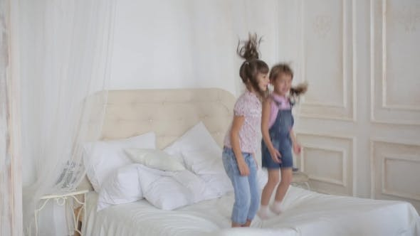 Thumbnail for Two Little Girls Playing And Jumping On The Bed