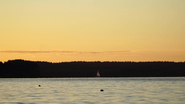 Thumbnail for A Small Sailing Boat On The Water At Sunset