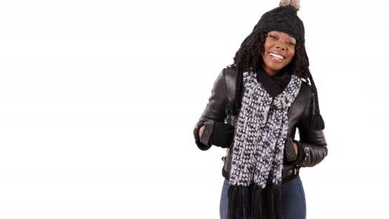 Thumbnail for Cute black female in winter clothes turns around to smile at camera in studio