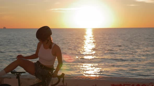 Cover Image for Summertime shot of young woman cyclist in stylish outfit is riding bicycle along beach promenade
