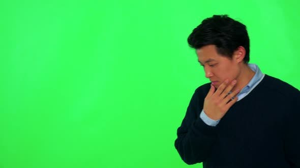 Thumbnail for A Young Asian Man Rubs His Chin, Looks Concerned and Walks Back and Forth - Green Screen Studio
