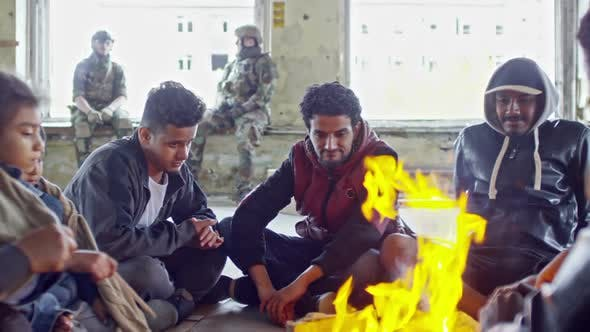 Thumbnail for Refugees Warming by Fire in Abandoned Building