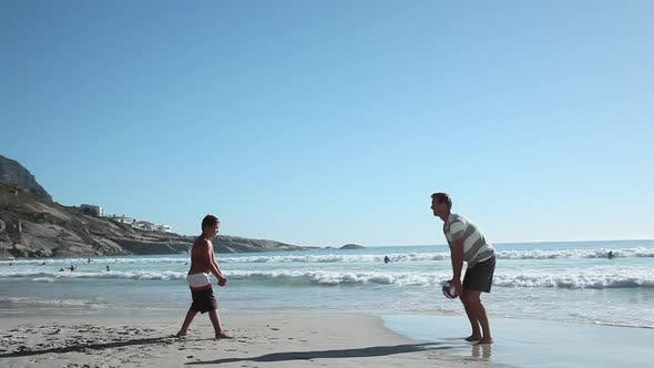 Thumbnail for Father and son playing ball on beach