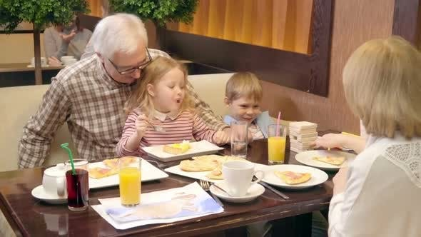 Thumbnail for Kids And Grandparents Eating and Playing at Dinner in Cafe
