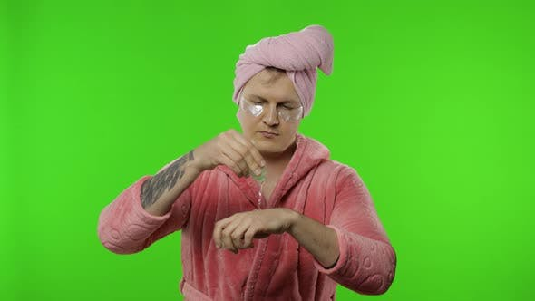 Thumbnail for Portrait of Transsexual Man in Bathrobe Applying Hand Moisturizing Cream