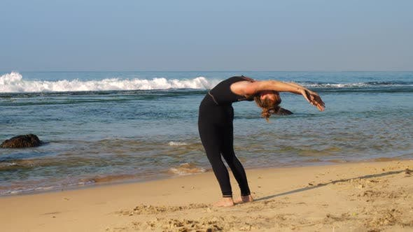 Thumbnail for Sporty Lady Exercises on Sandy Beach at Waving Ocean
