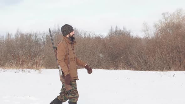 Thumbnail for Young Hunter in Warm Clothes Is on the Field with a Hunting Rifle.