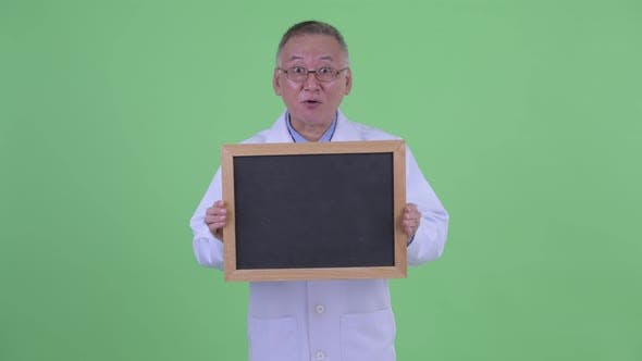 Thumbnail for Happy Mature Japanese Man Doctor Looking Surprised While Holding Blackboard